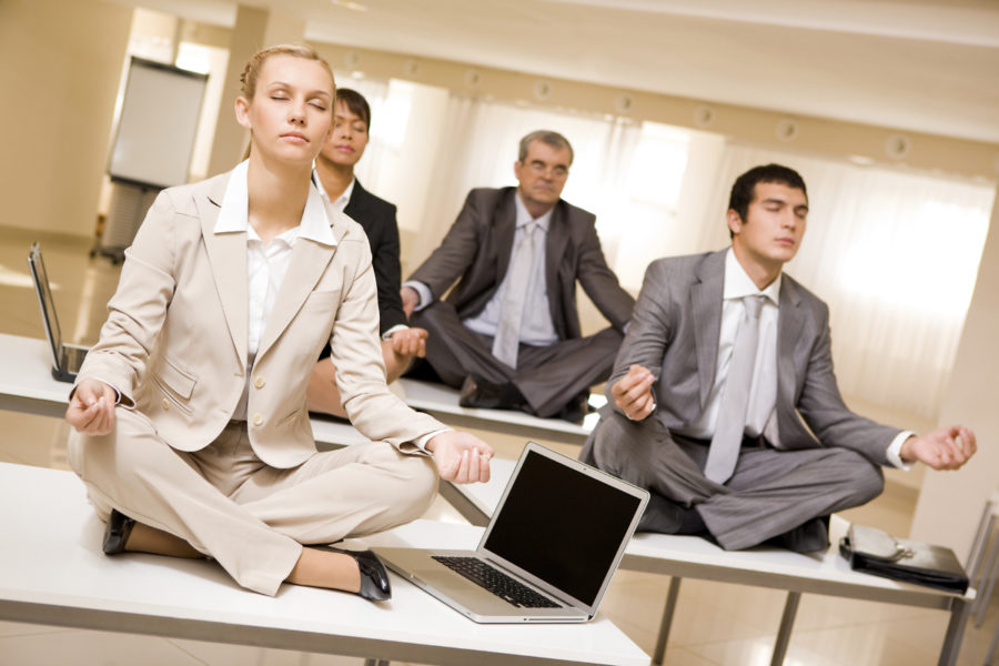 Personas meditando en la oficina