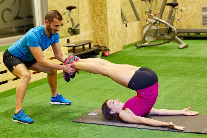Entrenador personal estirando las piernas de una chica