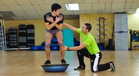 Entrenador personal haciendo un ejercicio para la recuperación de una lesión de rodilla